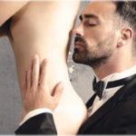 мъж миришещ гърба на жена, опиянен от парфюма с феромони, с който се е напръскала голата жена